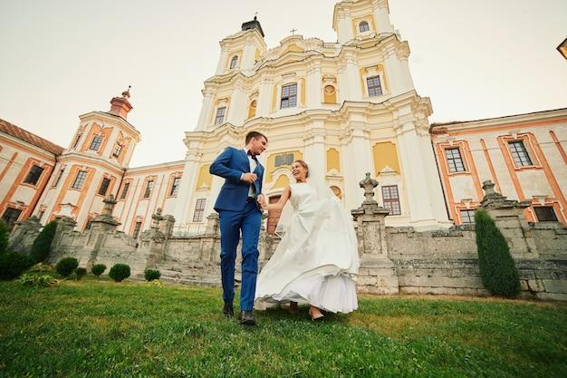 Gelukkig plezier jonggehuwden poseren in de tuin bij de kerk