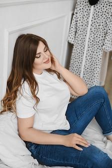 Gelukkig plus-size model meisje in spijkerbroek en wit t-shirt zittend op het bed in de ochtend. jonge mollige vrouw in een casual outfit poseren op het bed. lichaam positief. concept van unideale schoonheid. xxxl mode