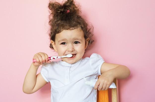 Gelukkig poetst weinig krullend meisje haar tanden met tandpasta. persoonlijke hygiënetraining voor het kind. kid schone mond. routine thuis badkamer procedure.