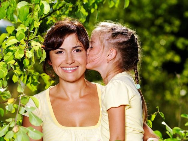 Gelukkig portret van de moeder en dochtertje buitenshuis