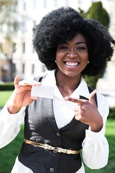 Gelukkig portret van een afrikaanse jonge zakenvrouw wijzende vinger naar visitekaartje
