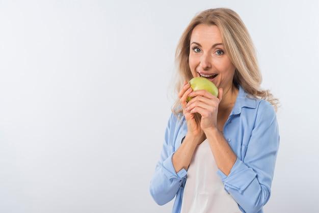 Gelukkig portret van een glimlachende jonge vrouw die groene appel eet tegen witte achtergrond