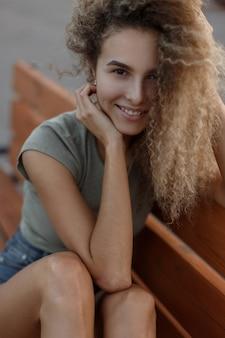 Gelukkig portret van een jong grappig krullend meisje buitenshuis