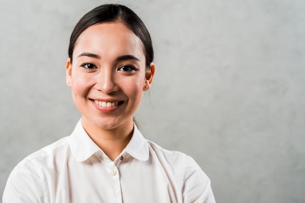 Gelukkig portret van een jonge aziatische onderneemster die zich tegen grijze achtergrond bevindt