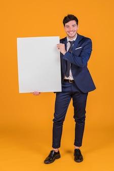 Gelukkig portret van een jonge zakenman die wit leeg aanplakbiljet toont dat ter beschikking houdt