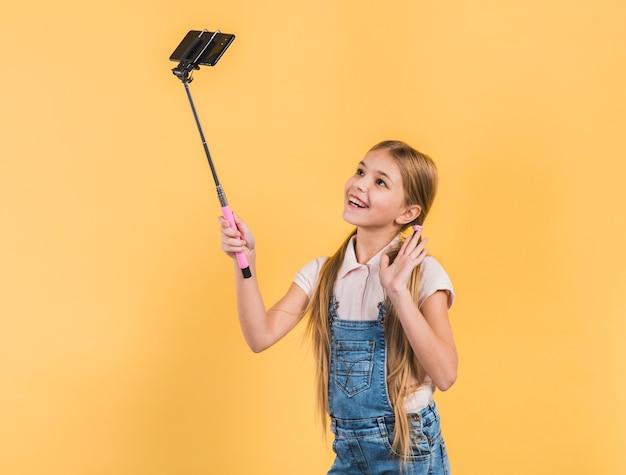 Gelukkig portret van een meisje die haar hand golven die selfie op mobiele telefoon tegen gele achtergrond nemen