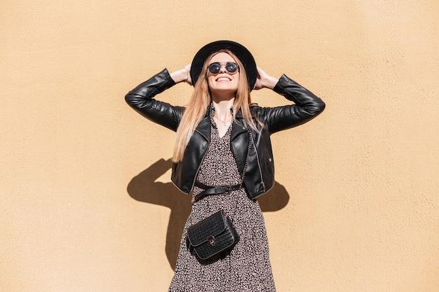 Gelukkig portret van een mooi modieus vrolijk hipstermeisje met een glimlach in een leren jas, hoed en vintage jurk met zonnebril en een modetas staat in de buurt van de muur in de stad