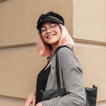 Gelukkig portret van een mooie glimlachende jonge vrouw met een bril en een hoed in een geruit hemd met een zwarte handtas in de buurt van de muur in de stad