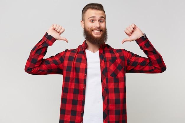 Gelukkig portret van een vrolijke blije blije trotse bebaarde man in geruit overhemd, gebalde vuisten en wijzende duimen op zichzelf als winnaar met ogen gesloten van plezier, geïsoleerd op witte achtergrond