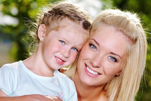 Gelukkig portret van jonge moeder en schattig dochtertje - over de aard