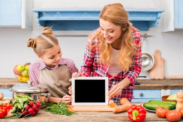 Gelukkig portret van moeder en dochter die digitale tablet op houten bureau bekijken