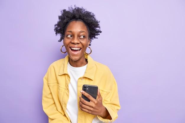 Gelukkig positief krullend tienermeisje met donkere huid houdt smartphone vast en kijkt aangenaam weg gekleed in gele jas maakt gebruik van moderne technologieën geïsoleerd op paars