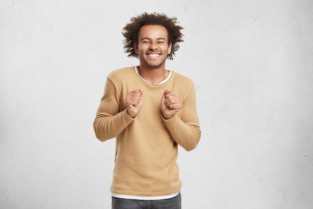 Gelukkig positief mannetje met borstelig krullend haar, steekt vuisten en grijnst naar de camera, heeft een heerlijke uitdrukking