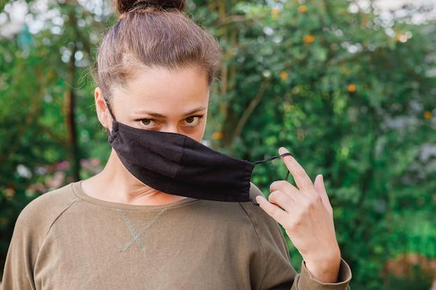 Gelukkig positief meisje doet een beschermend medisch masker af van het gezicht buitenshuis. jonge vrouw die masker verwijdert dat na vaccinatie glimlacht. coronavirus pandemie covid 19 concept. lentebloemen pollenallergie.