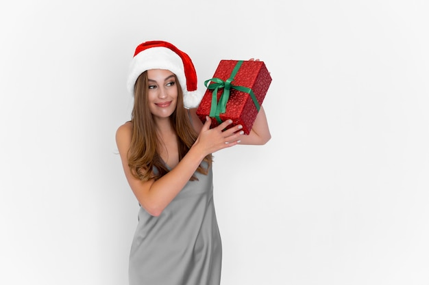Gelukkig positief meisje in een kerstmuts die een geschenkdoos schudt terwijl ze op een witte achtergrond staat