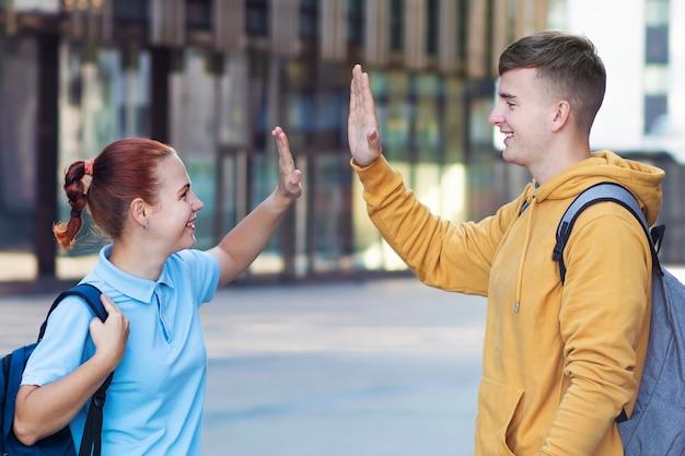 Gelukkig positief paar, twee succesvolle universiteitsstudenten die high five geven, permanent met rugzakken, glimlachend.