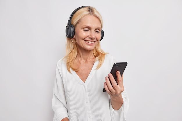 Gelukkig positieve blonde middelbare leeftijd mooie vrouw heeft videoconferentie houdt mobiele telefoon gericht op smartphone scherm maakt gebruik van draadloze koptelefoon draagt witte blouse poses binnen