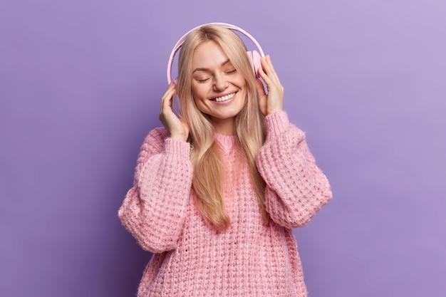 Gelukkig positieve blonde vrouw sluit de ogen en lacht tevreden luistert naar audiotrack via koptelefoon gekleed in casual gebreide trui