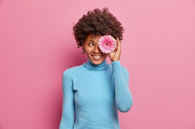 Gelukkig positieve donkere jonge vrouw bedekt oog met roze gerbera, brede glimlach, nonchalant gekleed, vormt indoor, geniet van de lentetijd.