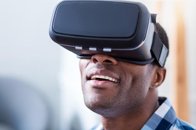 Gelukkig positieve jonge man op zoek naar 3d-bril en glimlachen tijdens het gebruik van de nieuwste technologie