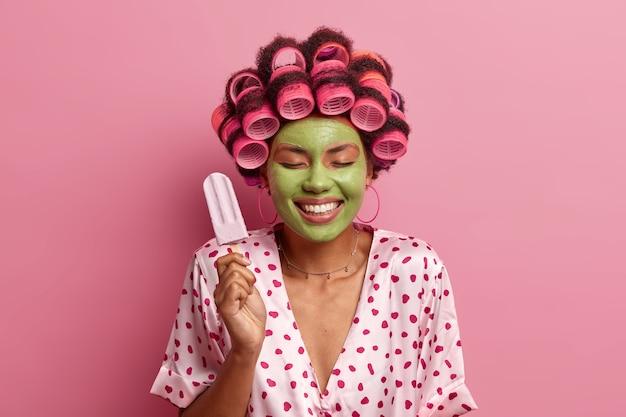 Gelukkig positieve jonge vrouw staat met gesloten ogen, houdt heerlijk ijs, past haarrollers toe, maakt krullend kapsel, geeft om teint, draagt groene schoonheidsmasker, toont witte tanden