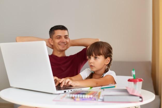 Gelukkig positieve man zit met opgeheven kijken naar zijn dochter die aan tafel zit en kijkt naar lap top display met bange uitdrukking, familie poseren thuis.