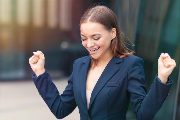 Gelukkig positieve succesvolle mooie, opgewekte opgewonden zakenvrouw