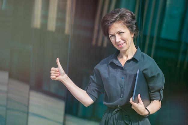 Gelukkig positieve volwassen volwassen zakenvrouw permanent buitenshuis business center met laptop computer weergegeven: duim omhoog, zoals gebaar, glimlachend.