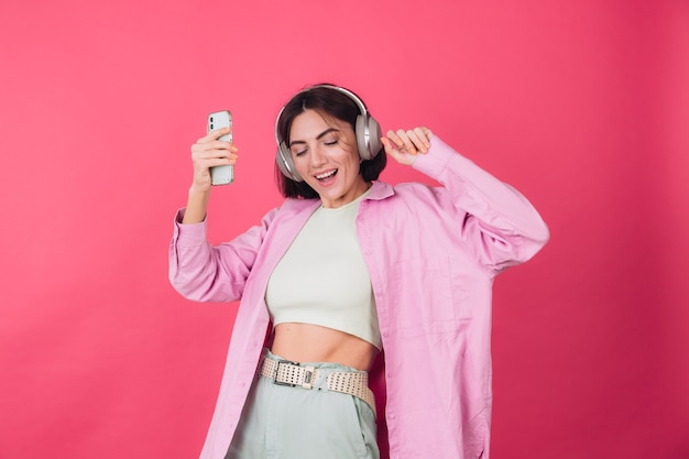 Gelukkig positieve vrouw in koptelefoon op roze rode muur