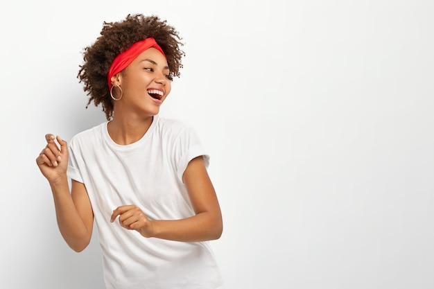 Gelukkig positieve vrouw kijkt graag weg, danst op het ritme van muziek, houdt het hoofd weggedraaid, gekleed in vrijetijdskleding
