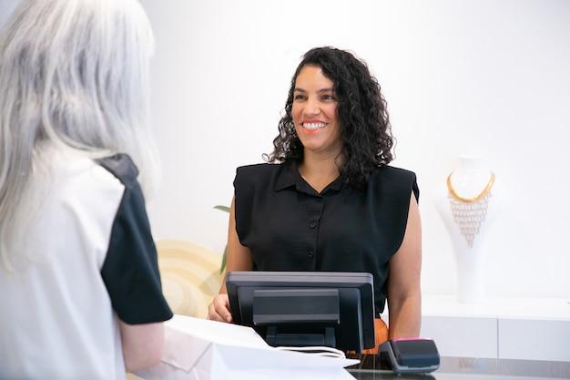 Gelukkig positieve winkel kassier in gesprek met de klant en lachen bij het afrekenen. gemiddeld schot. winkelen concept