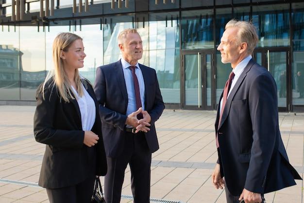 Gelukkig positieve zakenpartners bijeen op kantoorgebouw, staan en praten buiten, deal bespreken. gemiddeld schot, zijaanzicht. samenwerking concept