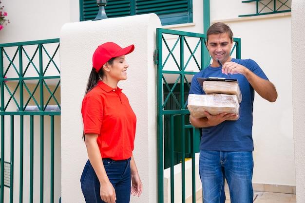 Gelukkig postbode wachten wanneer cliënt inlogt op klembord, glimlachend en staand. blanke klant van middelbare leeftijd met kartonnen dozen of pakketten. bezorgservice en online winkelconcept