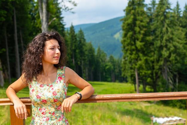 Gelukkig prachtig meisje geniet van uitzicht op de bergen verblijf in zomerjurk op de heuvel met adembenemend berglandschap.