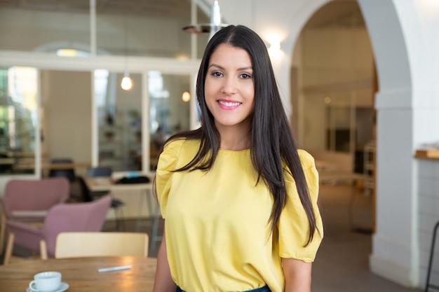 Gelukkig prachtige zwartharige vrouw, gekleed in geel shirt, permanent in co-werkruimte, poseren,