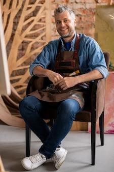 Gelukkig professionele kunstenaar in werkkleding op zoek naar jou met brede glimlach zittend in een stoel in de studio