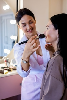 Gelukkig professionele make-up artiest cosmetica lip potlood toe te passen op vrouw cliënt werkende schoonheidssalon