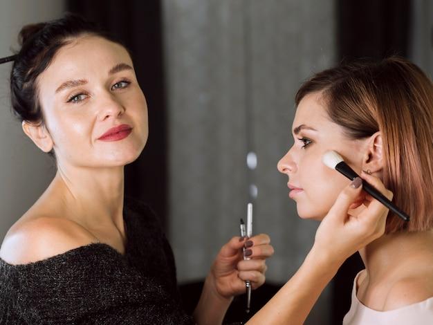 Gelukkig professionele make-up artist aan het werk