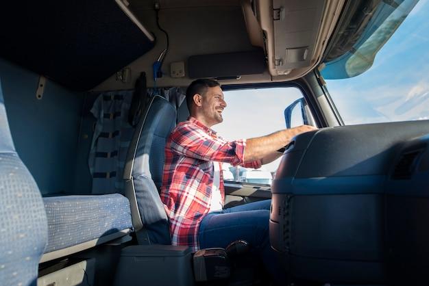 Gelukkig professionele vrachtwagenchauffeur van middelbare leeftijd in casual kleding vrachtwagen rijden op snelweg