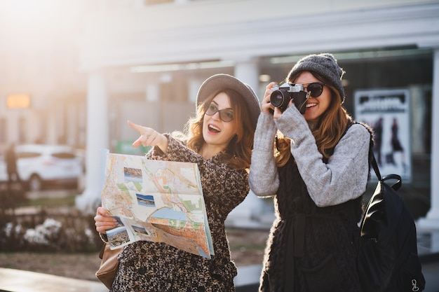 Gelukkig reizen samen van twee modieuze vrouwen in het zonnige stadscentrum. jonge blije vrouwen die positiviteit uiten, kaart gebruiken, vakantie met tassen, camera, foto maken, vrolijke emoties, goed humeur.
