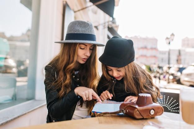 Gelukkig reizend gezin. jonge moeder met dochter zitten in café op de achtergrond van de zonnige stad, kijk naar de kaart. moeder en kind hebben plezier aan tafel. ze zijn stijlvol gekleed, goed humeur.