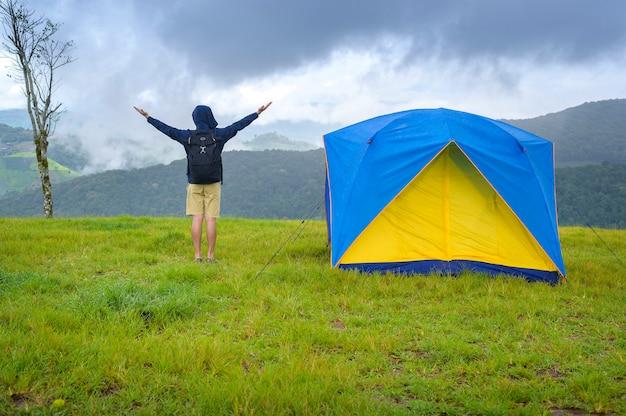 Gelukkig reizende man genieten en ontspannen in de buurt van camp tent