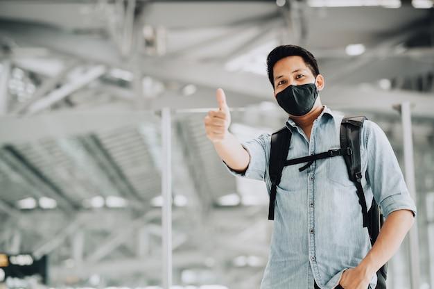 Gelukkig reiziger aziatische man met masker beschermt tegen coronavirus met duim omhoog met vertrouwen
