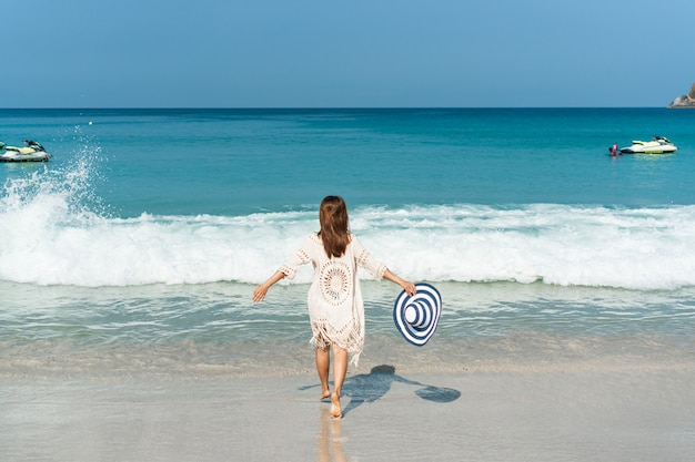 Gelukkig reiziger aziatische vrouw geniet op tropisch strand op vakantie. zomer op strand concept.