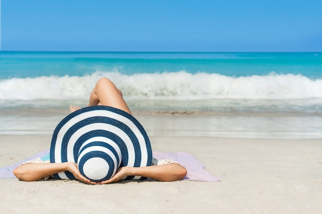 Gelukkig reiziger aziatische vrouw genieten van zonnebaden op tropisch strand op vakantie.