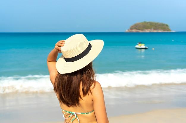 Gelukkig reiziger aziatische vrouw in bikini met strand-hoed geniet op tropisch strand op vakantie. zomer op strand concept.
