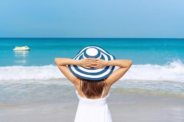 Gelukkig reiziger aziatische vrouw in witte jurk geniet op tropisch strand op vakantie