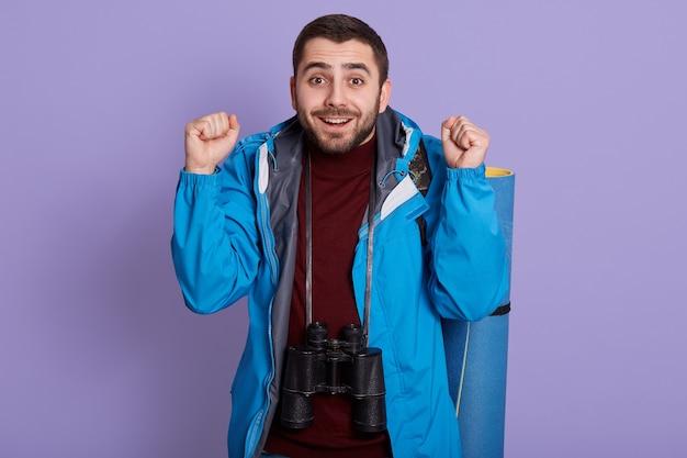 Gelukkig reiziger jonge man in blauwe casual jas met rugzak geïsoleerd op paarse achtergrond. toerist die op weekenduitstap reist