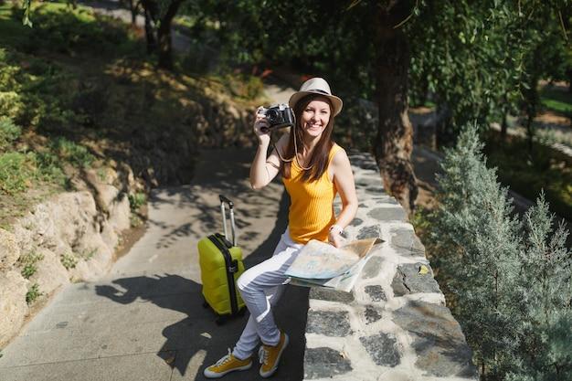 Gelukkig reiziger toeristische vrouw in hoed met koffer, stadsplattegrond foto's maken op retro vintage fotocamera in de stad buiten. meisje dat naar het buitenland reist om een weekendje weg te reizen. toeristische reis levensstijl.