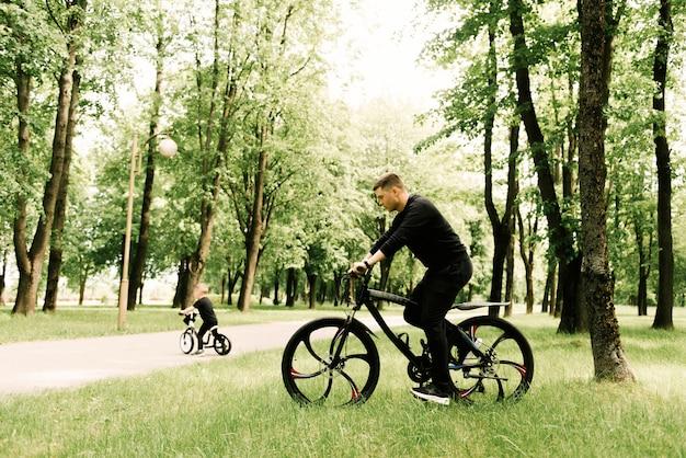 Gelukkig rijdt kleine jongen een fiets met een jonge vader in het park